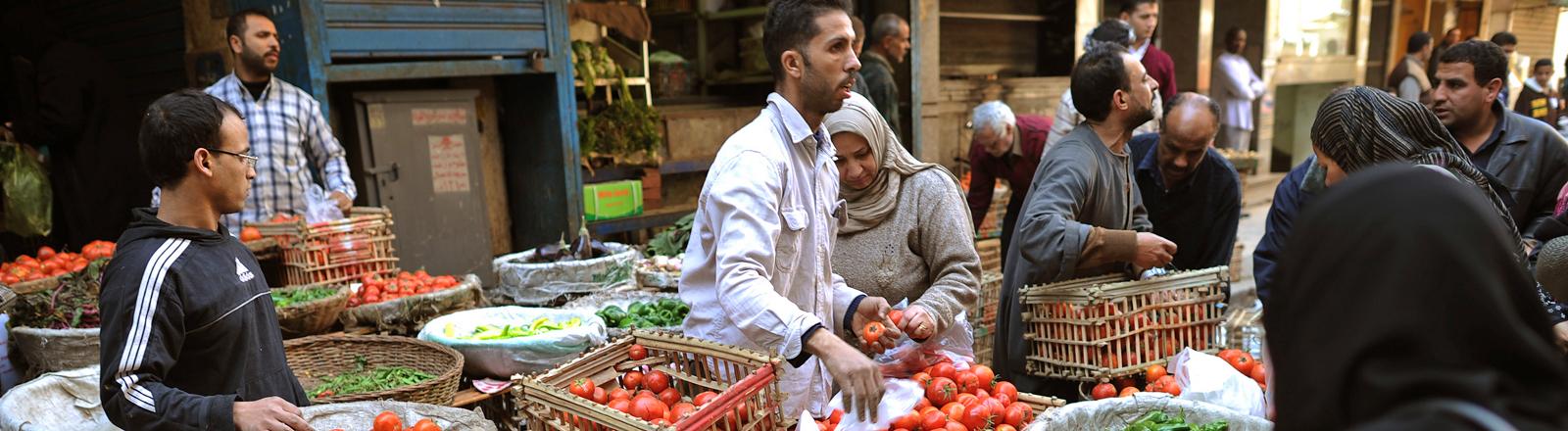 Händler stehen hinter einem Marktstand und verkaufen Gemüse, vor allem Tomaten; Bild: dpa