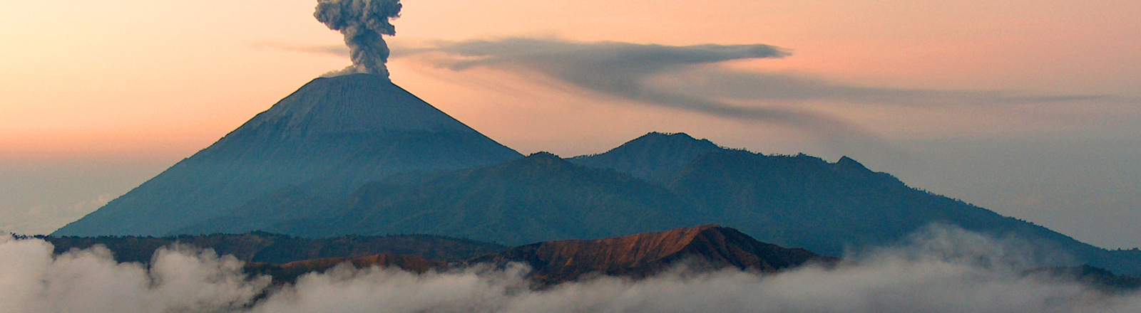 Aus einem Vulkan steigt Rauch auf.