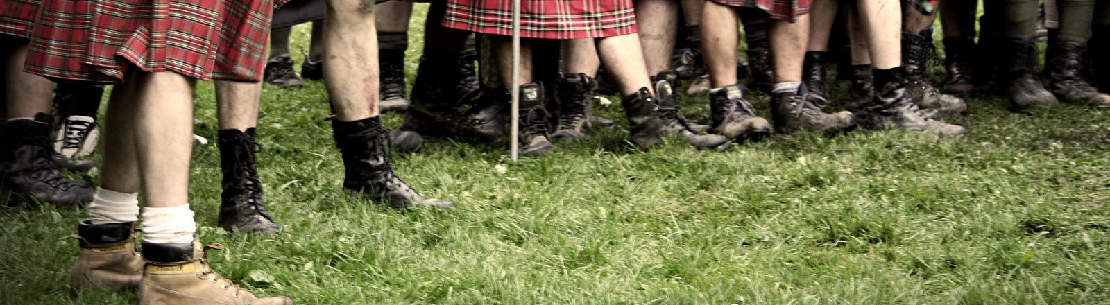 Männer stehen nebeneinander bekleidet mit Schottenröcken. Es sind nur die Röcke, nackten Waden und Schuhe zu sehen.
