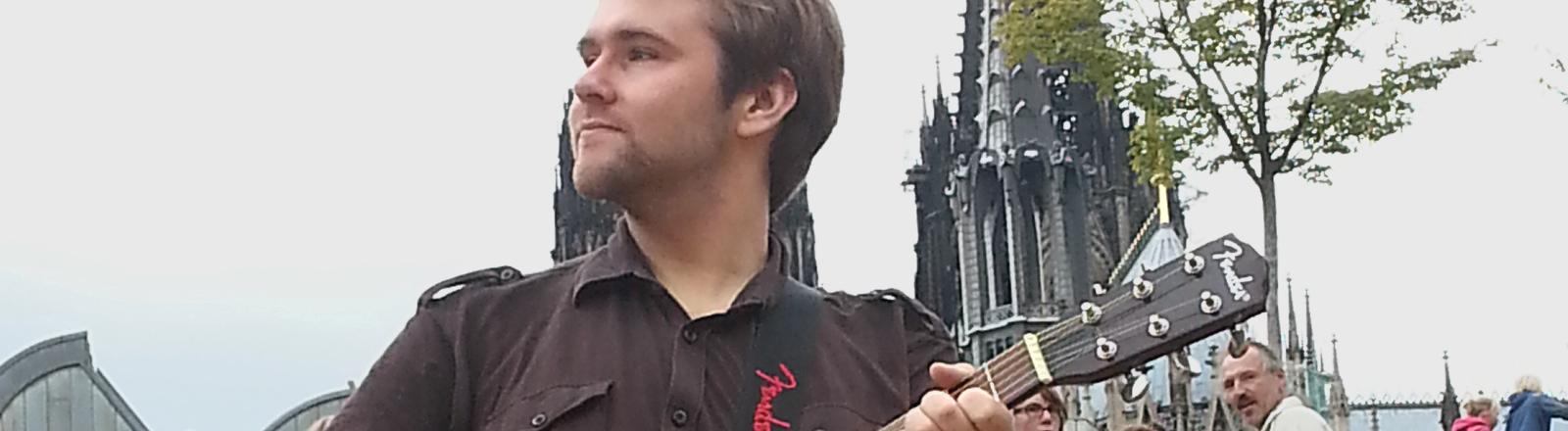 Renardo Schlegelmilch spielt Gitarre und blickt in die Ferne. Im Hintergrund stehen Passanten. Die Spitzen des Kölner Doms sind zu sehen.