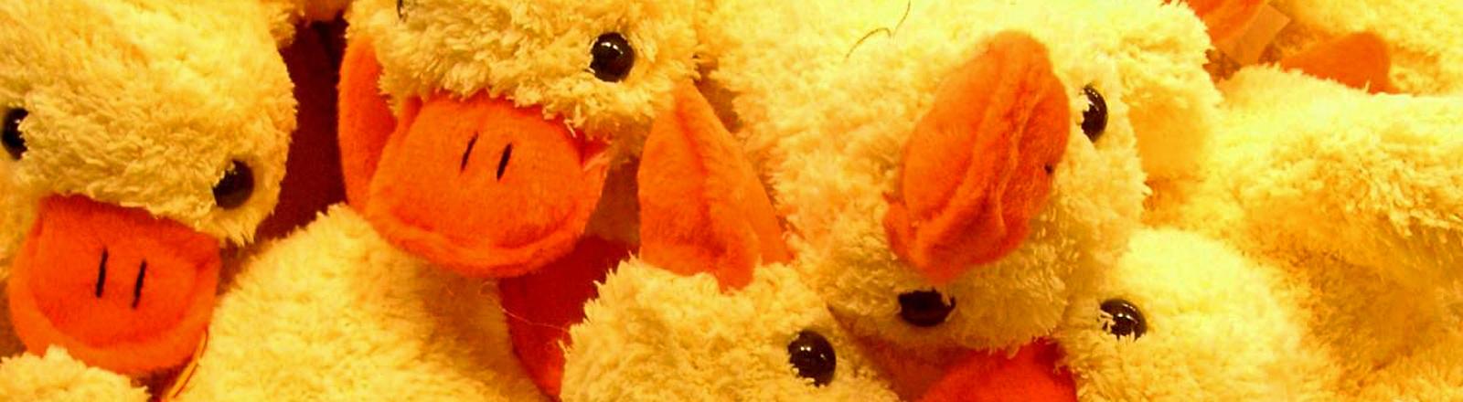Gelbe Kuscheltiere in Form von Enten liegen auf einem Haufen. Mit schwarzen Knopfaugen und orangenen Schnäbeln.