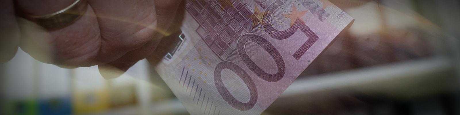 Eine Hand nimmt einen 500-Euro-Geldschein entgegen.