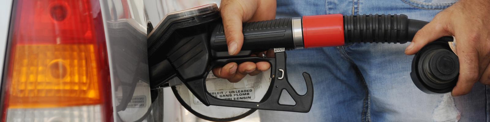 Ein Mann steht an der Tankstelle und führt den Zapfhahn in den Tank.