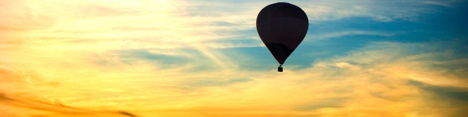 Ein Ballon fliegt in der Morgendämmerung.