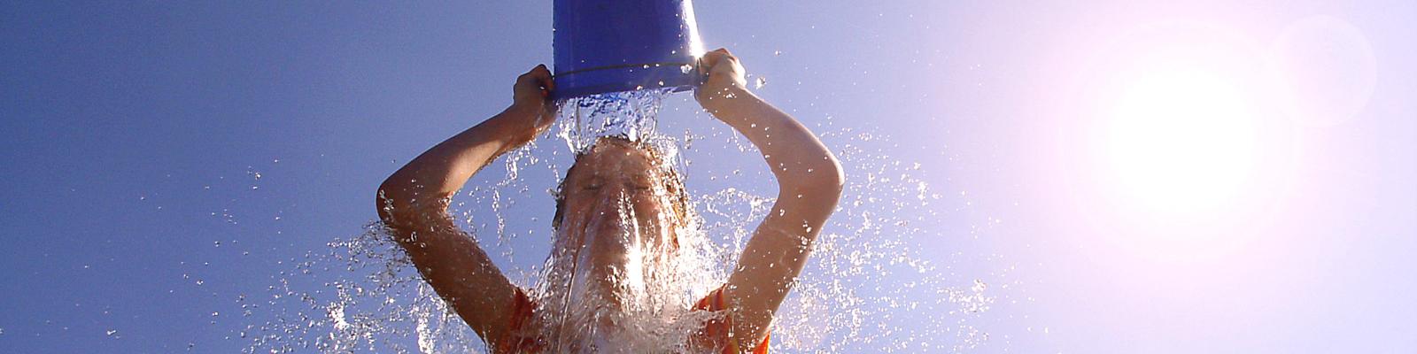 Eine Frau schüttet sich einen Eimer Wasser über den Kopf.