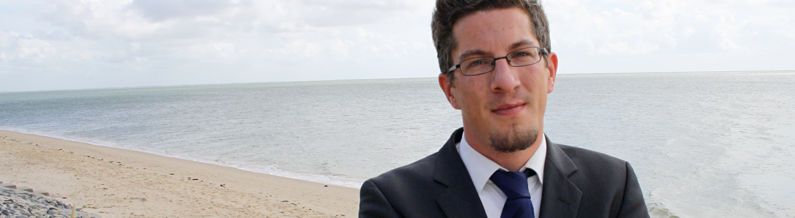 Daniel Köhler steht am Strand, im Hintergrund das Meer. Er hat kurze, dunkle Haare. Er trägt eine Brille und Anzug mit Schlips.