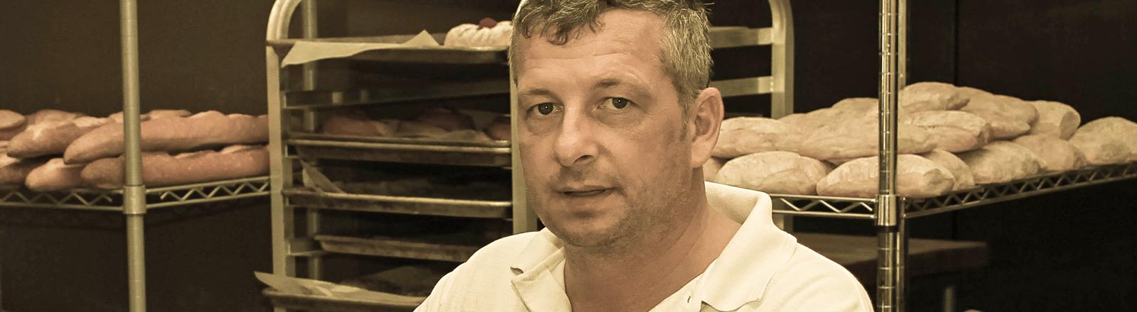 Markus Saffert steht in seiner Bäckerei. Hinter ihm liegen in Regalen Brötchen und Baguettes. Saffert hat kurze, leicht ergraute Haare und braune Augen.