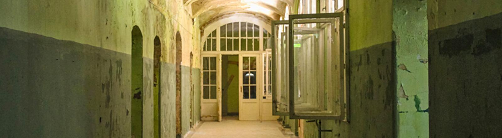 Ein langer Flur mit Türen rechts und Fenstern links, die offen stehen. Die Farbe blättert von den Wänden. Am Flurende ist eine große Holztür mit Fenstern.