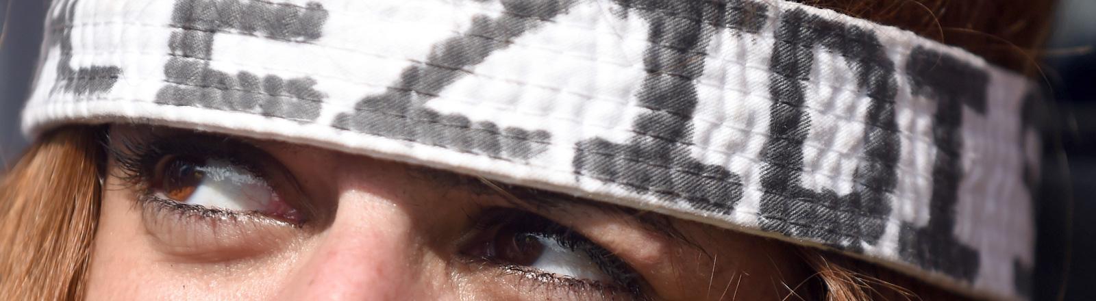 Eine Frau trägt ein Kopfband, auf dem Ezidi steht. Ihre Augen und das Band sind zu sehen.