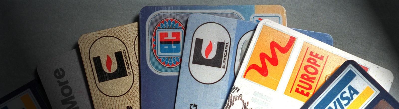Eine Reihe von Kreditkarten liegt aufgefächert nebeneinander, Blick von oben; Bild: dpa