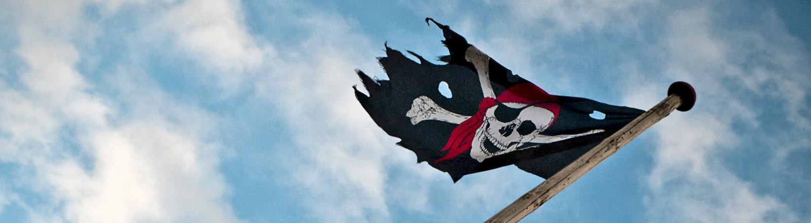 Eine Piratenfahne flattert im Wind. Blauer Himmel. Die Fahne ist teils zerrissen.