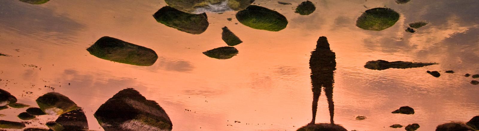 Schatten eines Menschen vor orangenfarbenem Hintergrund. Steine fliegen durch die Luft.