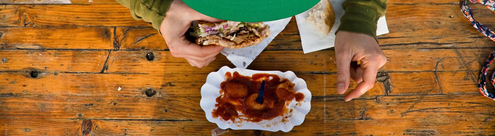 Blick von oben auf einen Tisch, auf dem eine Currywurst steht. Ein Mann, dessen Schirmmütze zu sehen ist, hält einen Döner Kebap in der Hand.