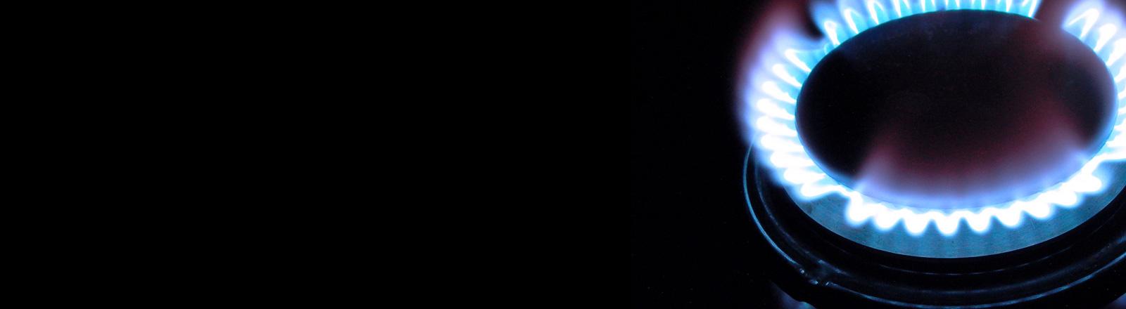 Vor schwarzem Hintergrund leuchtet die Gasflamme eines Herdes.