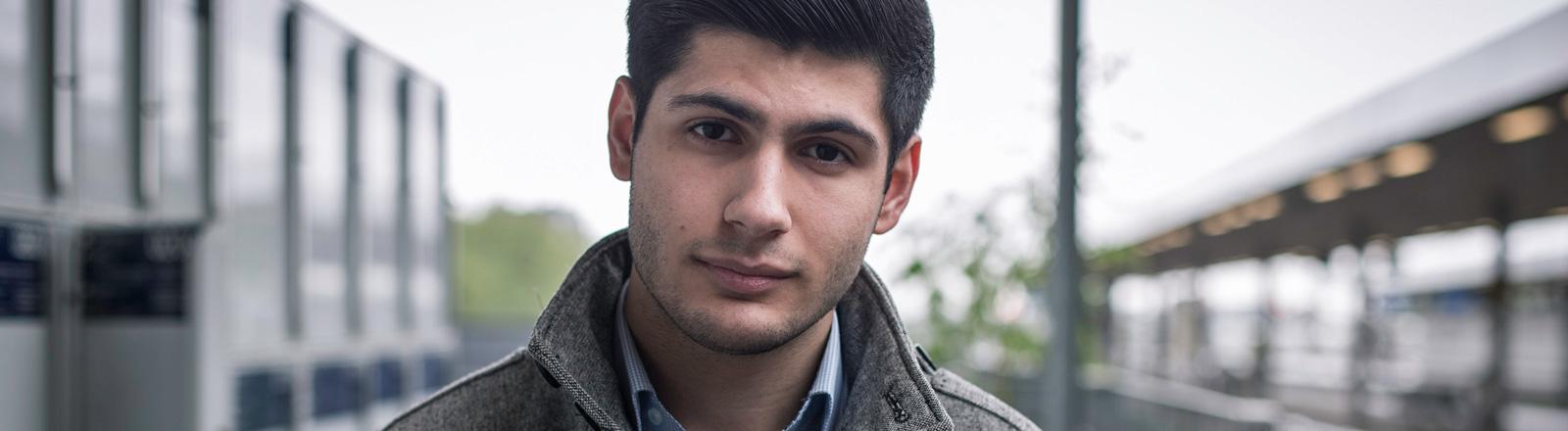Portrait von Sina Aaron Moslehi. Ein junger Mann mit schwarzen, kurzen Haaren. Er trägt Hemd und eine graue Jacke.