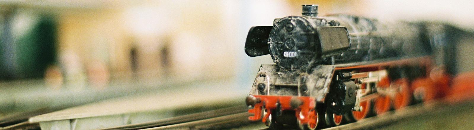 Eine schwarze Modelleisenbahn mit roten Rädern. Nachbau einer Dampflok.