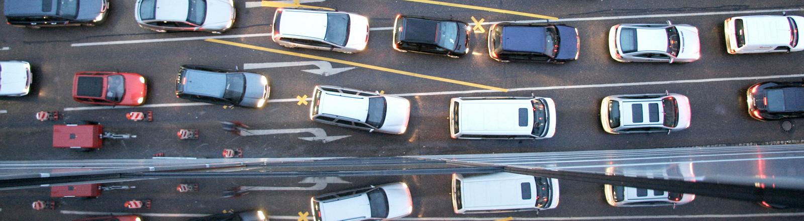 Blick von oben auf eine mehrspurige Straße, auf den Fahrbahnen stehen Autos hintereinander in der Schlange.