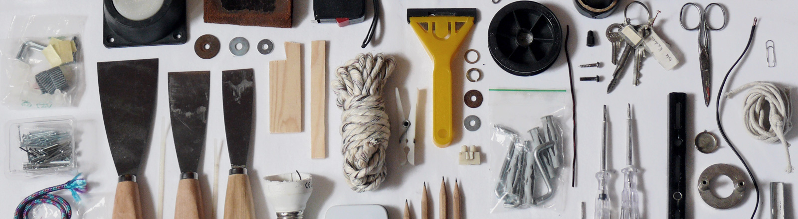 Blick auf Werkzeuge, die nebeneinander liegen. Seil, Schraubenzieher, Dübel, Nägel und anderes.