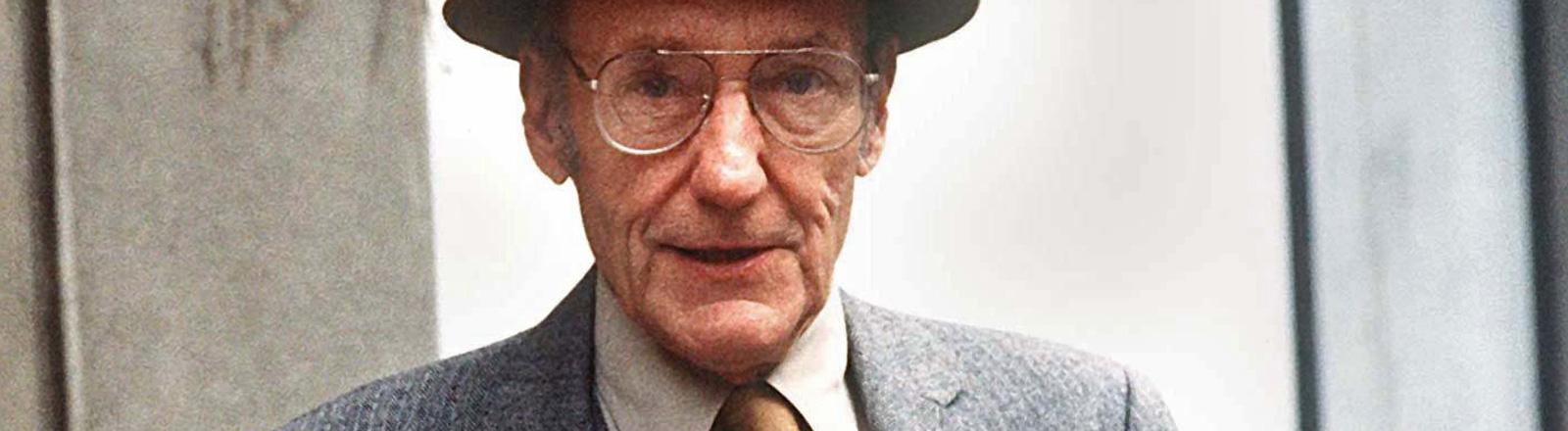 Portrait von William S. Burroughs im Alter von 70 Jahren. Er trägt Hut, Brille und Anzug; Bild: dpa
