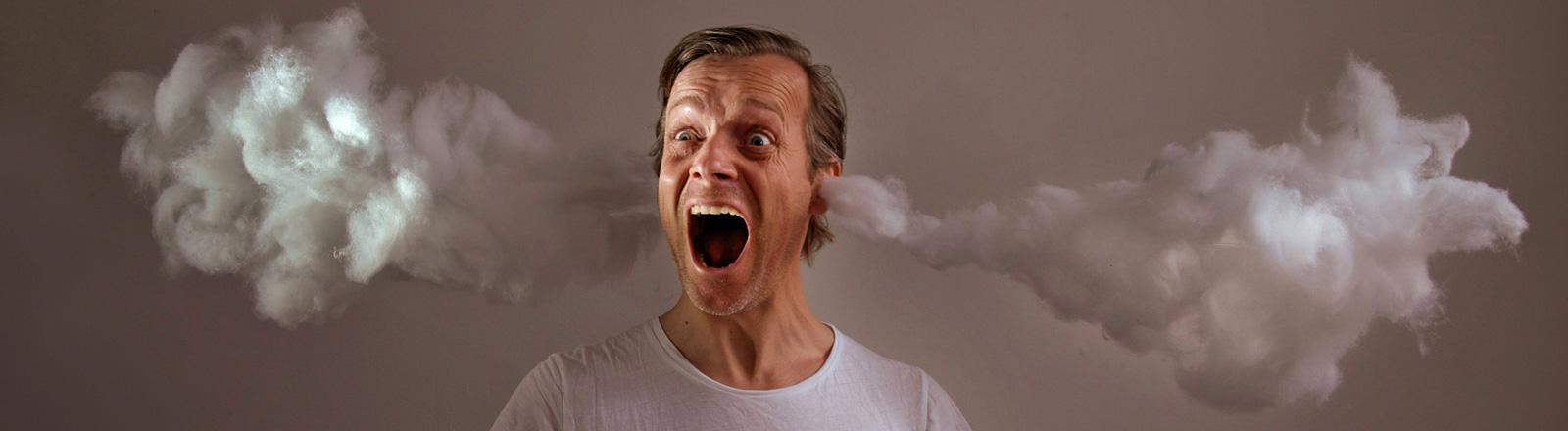 Ein Mann im weißen T-Shirt hat den Mund weit geöffnet. Aus seinen Ohren dringen weiße Wolken, die Watte ähneln.
