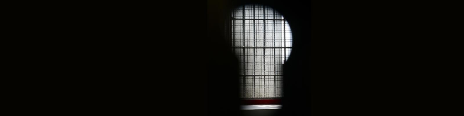 Blick durch ein freies Schlüsselloch in eine Zelle mit vergittertem Fenster der Sicherungsverwahrung  in der Justizvollzugsanstalt Schwalmstadt.