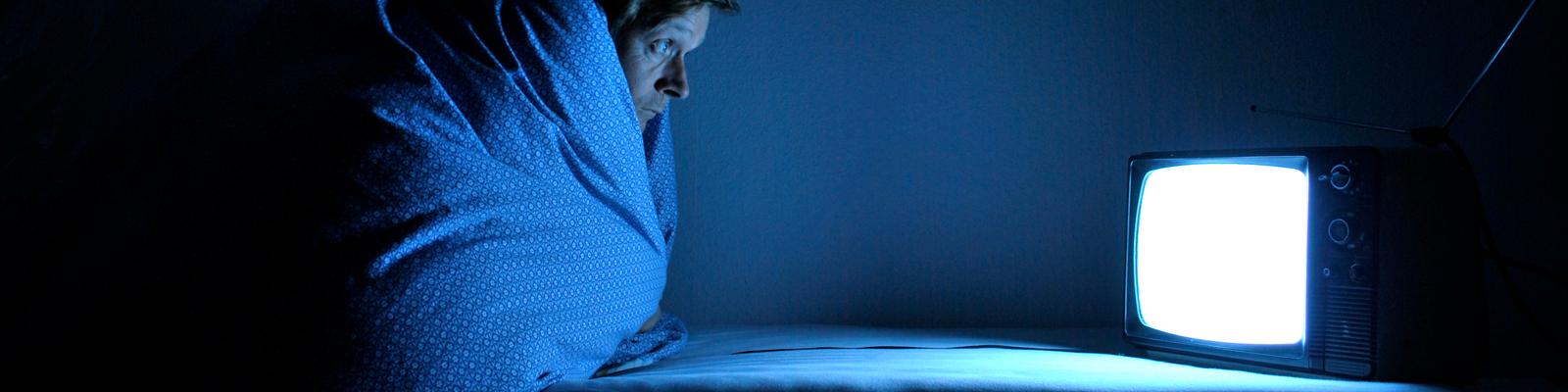 Ein Mann sieht in eine Bettdecke eingewickelt fern.