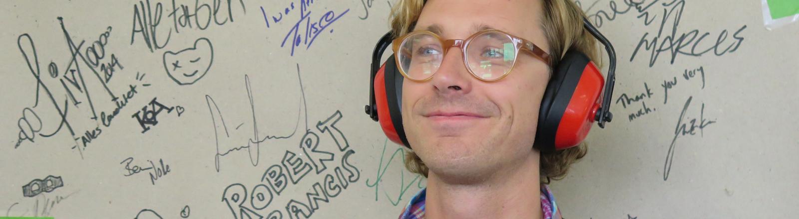 Der Popstar-Nerd Erlend Øye steht vor der Bandwand bei DRadio Wissen am 10.09.2014.