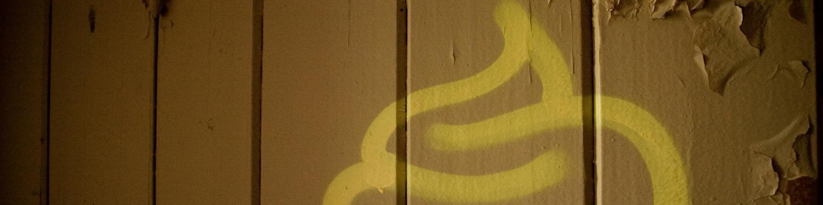 Ein Kothaufen auf eine Bretterwand gesprüht.