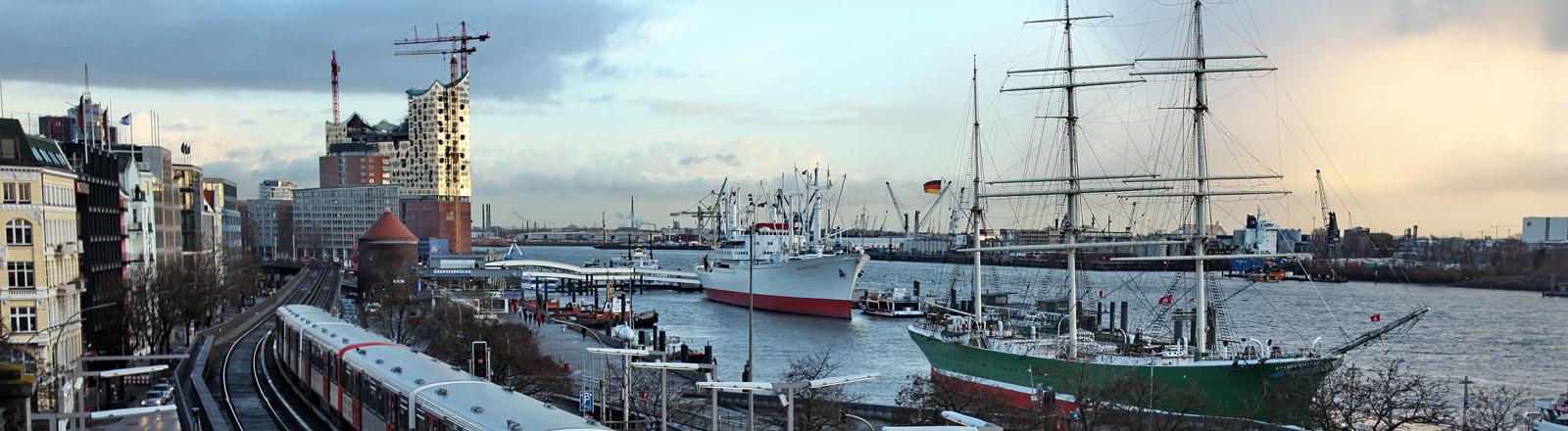 Die Haltestelle Landungsbrücken der Hamburger Hochbahn mit Hafen, Museumsschiffen und Elbphilharmonie im Hintergrund.