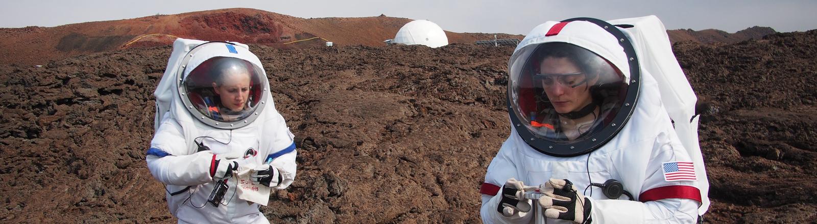 Während einer simulierten Marsmission auf Hawaii (USA) führt am 02.05.2014 DLR-Wissenschaftlerin Lucie Poulet (r) auch geologische Experimente durch. Dazu trug die Wissenschaftlerin einen Raumanzug, um die Simulation möglichst realitätsnah auszuführen.