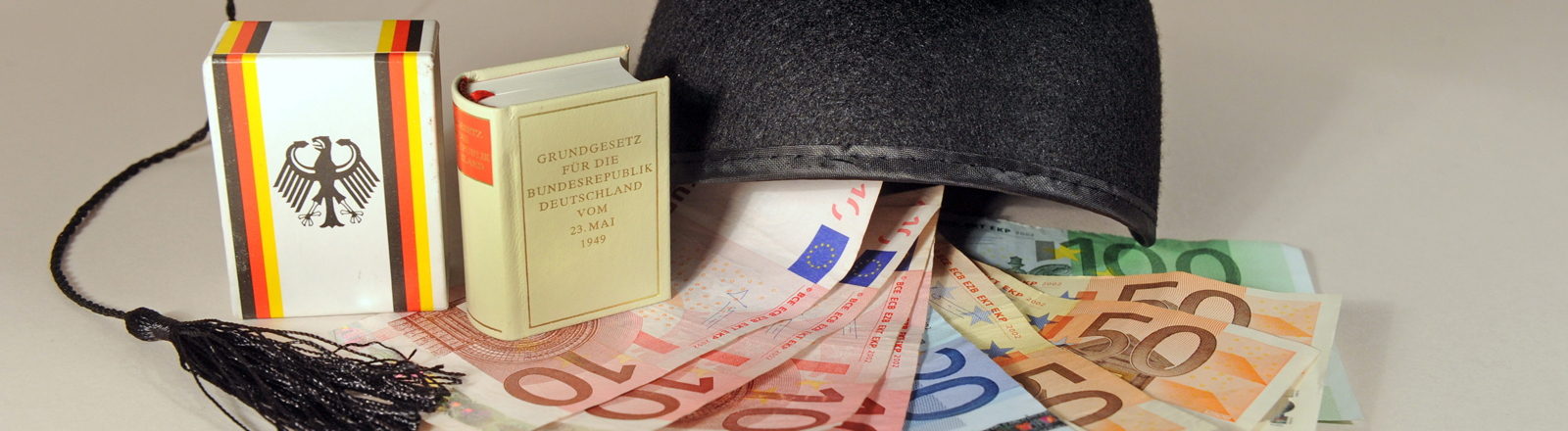 Euroscheine und Gesetzbuch liegen auf einem Tisch