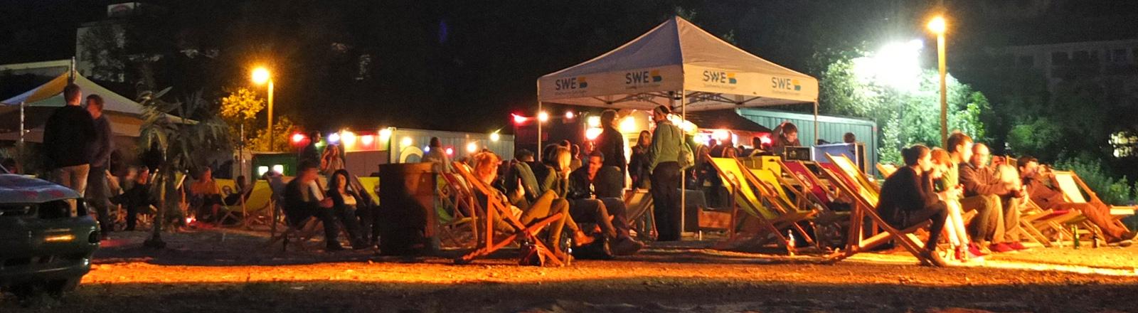 Menschen sitzen auf Klappstühlen draußen. Es ist Nacht und bunte Lampen leuchten.
