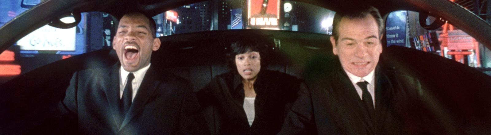 Die Schauspieler Smith, Lee Jones und Dawson sitzen, in einer Filmszene aus Men in Black, in einem futuristischen Auto und schauen panisch; Bild: dpa