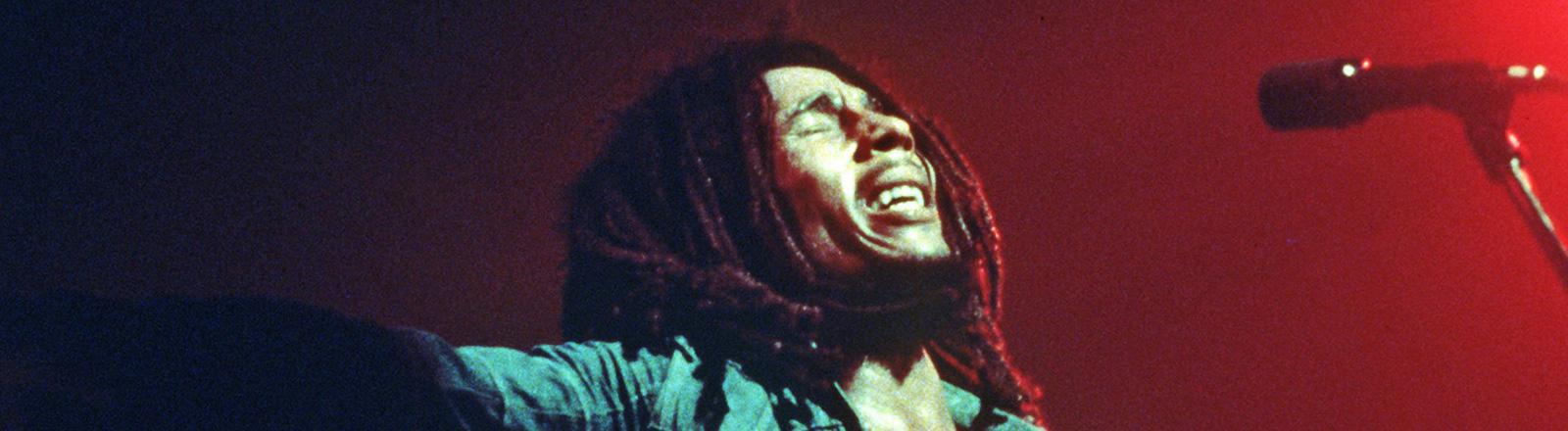 Bob Marley bei einem Konzert. Er hält die Augen geschlossen und schaut schmerzvoll. Vor ihm ist ein Mikrophon; Bild: dpa