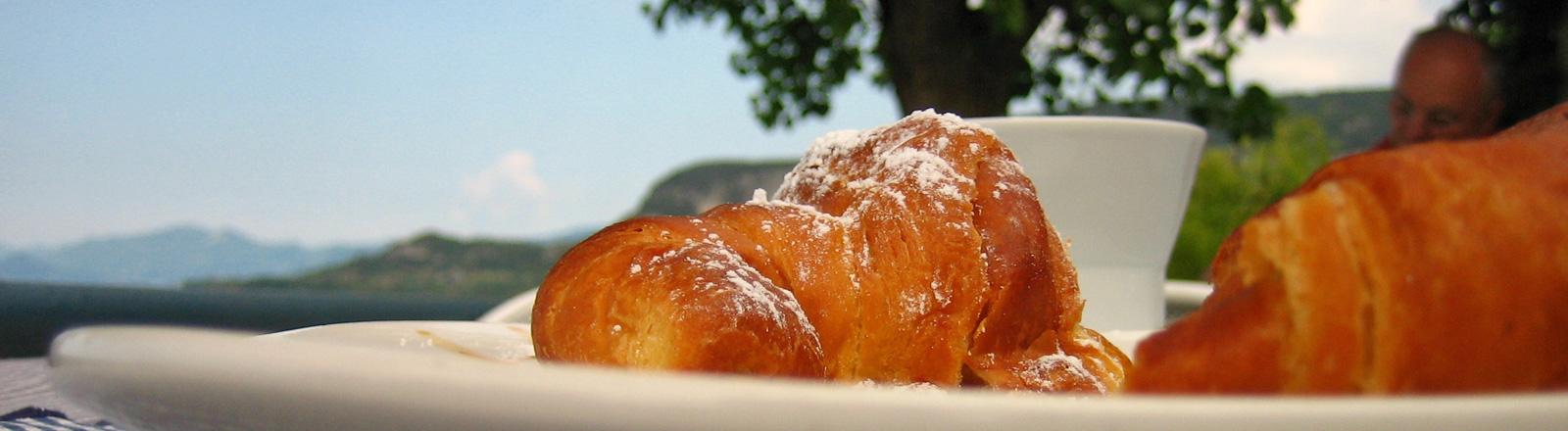 Auf einem Teller liegen Croissants. Dahinter steht eine Kaffeetasse. Dahinter sind Berge zu sehen. Blauer Himmel.