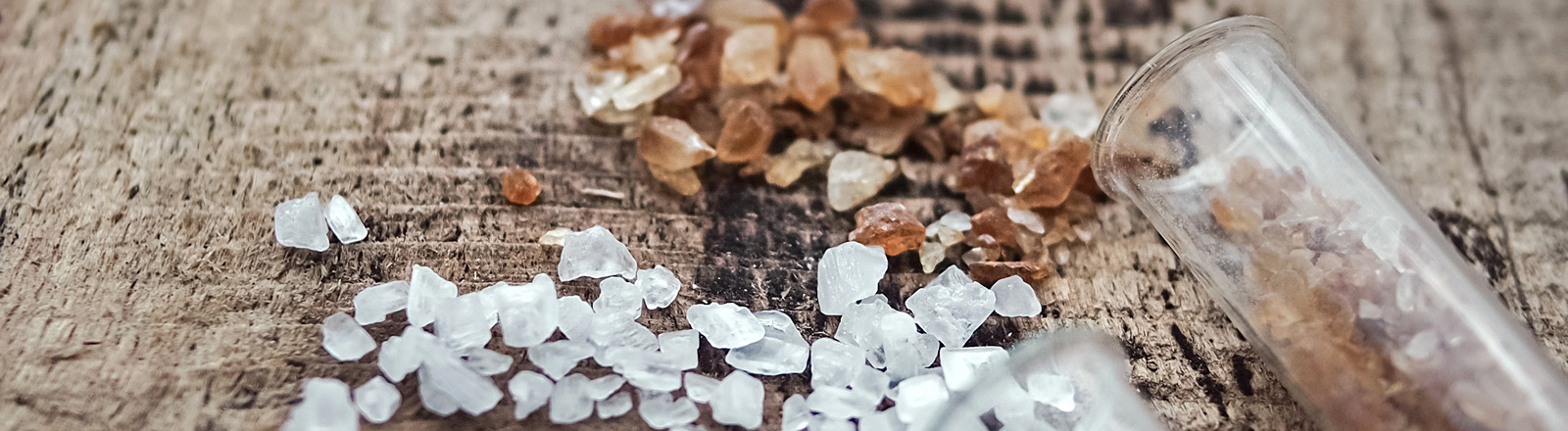 Auf Holz liegen weiße und braune Zuckerstücke sowie zwei gläserne Röhrchen.
