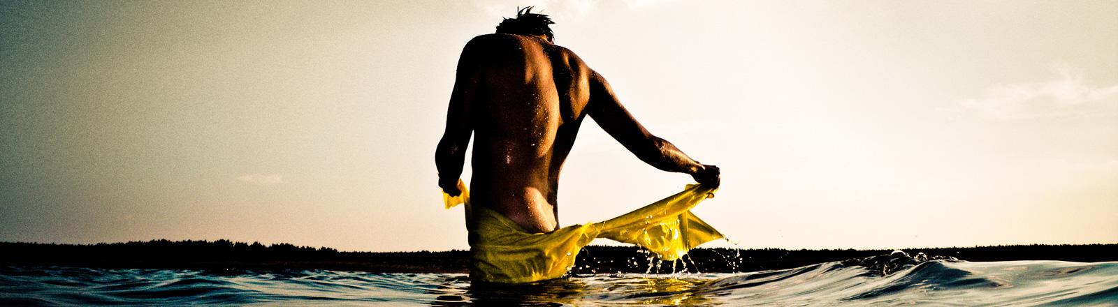 Ein muskulöser Mann steht nackt im Wasser, das ihm bis über die Knie reicht. Er ist von hinten zu sehen und legt sich eine Badehose um die Hüften.