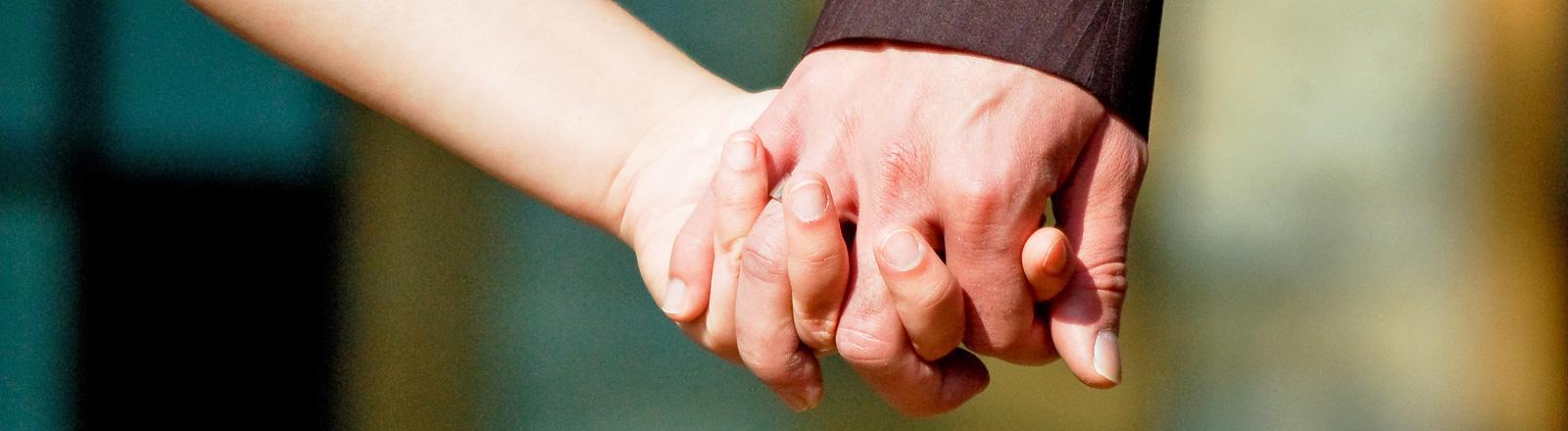 Zwei Hände greifen ineinander.
