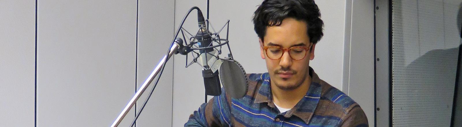 Luke Sital-Singh sitzt im Studio. Vor sich ein Mikrofon, er blickt nach unten.