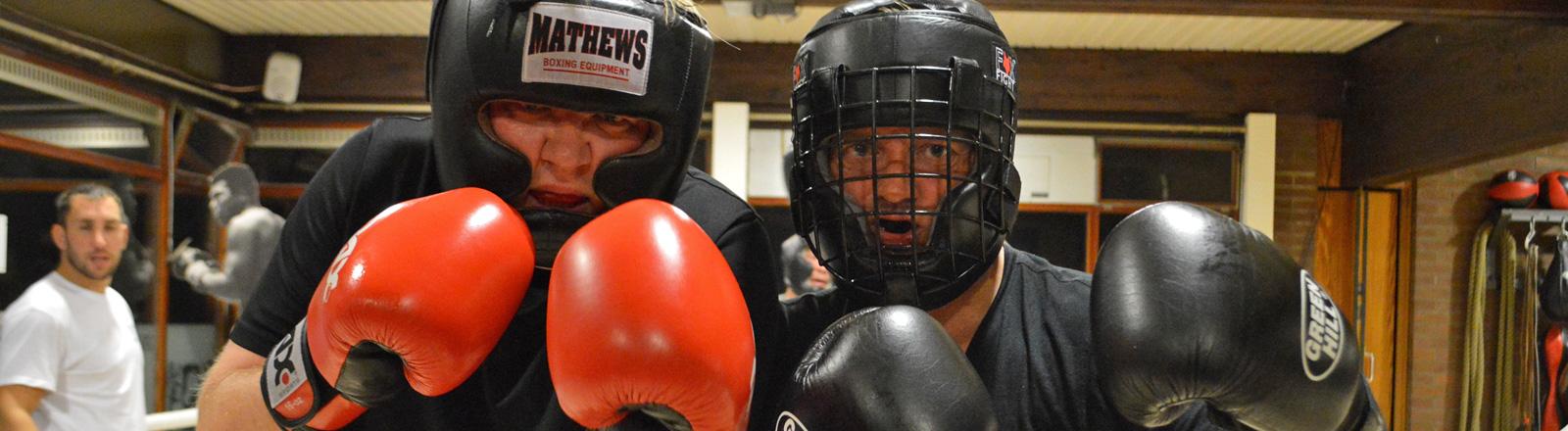 Zwei Männer in schwarzen T-Shirts, mit Boxhandschuhen und Gesichtsschutz stehen nebeneinander in einer Boxhalle. Sie halten die Hände nach oben und wirken kämpferisch.