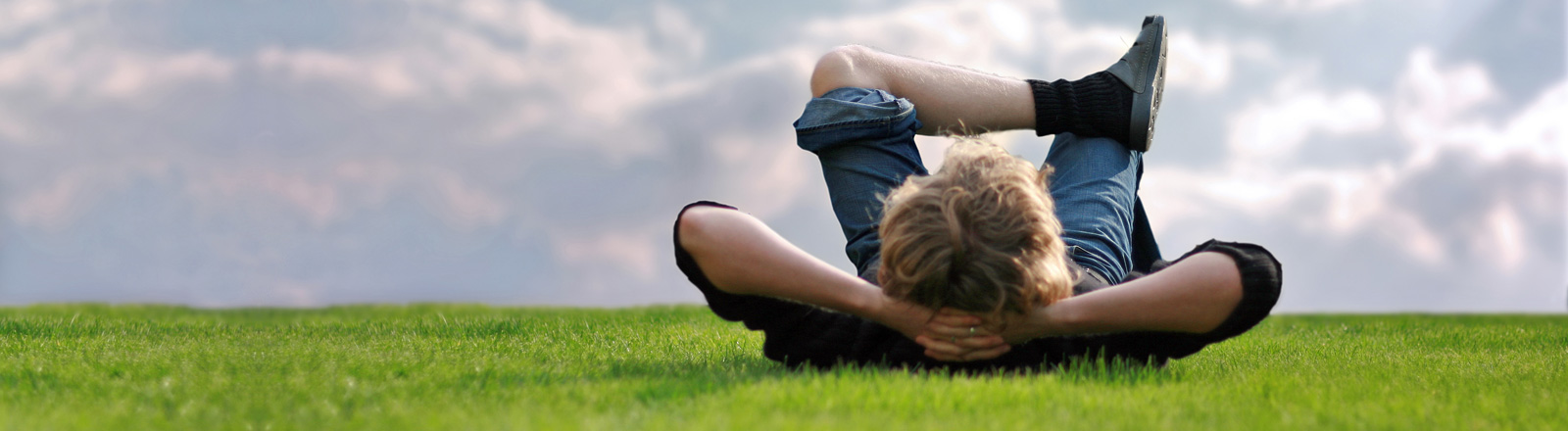 Ein Mann liegt auf einer grünen Wiese auf dem Rücken. Die Hände hat er hinter dem Kopf verschränkt. Das rechte Bein angewinkelt und das linke darüber gelegt.