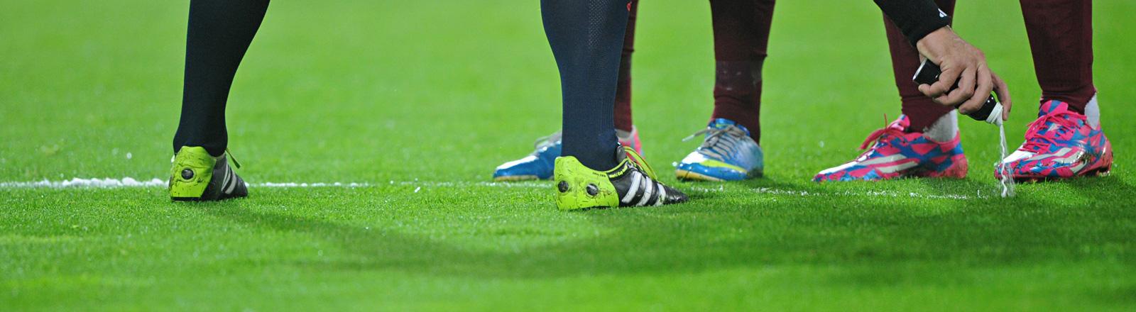 Auf einem Fußballrasen stehen drei Männer mit schwarzen Stulpen und Fußballschuhen. Ihre Beine sind bis zum Knie zu sehen. Eine Hand hält eine Spraydose und markiert damit den Boden; Bild: dpa
