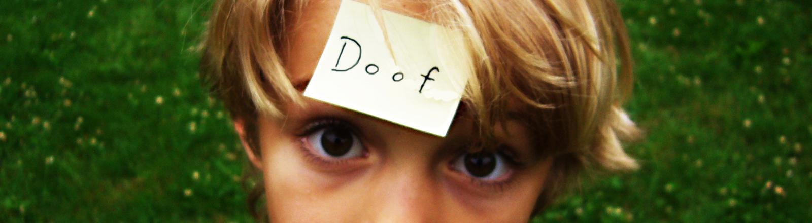 """Ein kleiner Junge hat auf der Stirn einen Zettel kleben, auf dem """"Doof"""" steht."""