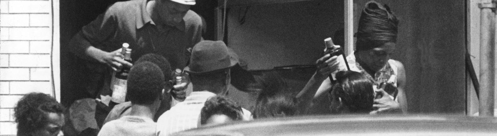 Nach den Rassenunruhen in Detroit 1967 plündern Afroamerikaner einen Laden aus