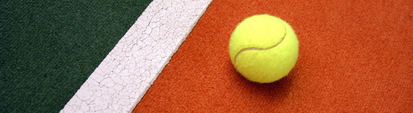 Ein Tennisball auf einem künstlichen Tennisplatzbelag.