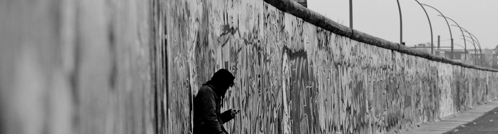 Ein Mann lehnt an der Berliner Mauer.