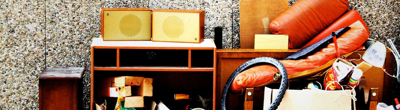 Sperrmüll vor einem Haus - Bananenkiste, Sessel, Lautsprecher und alte Möbel.