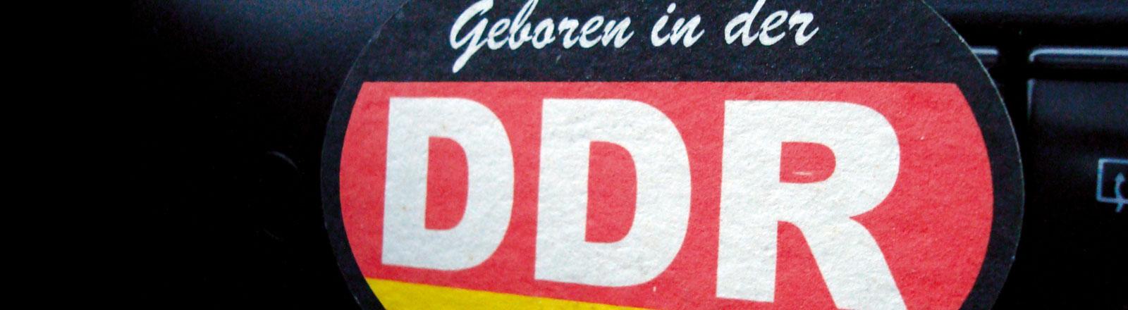 """Ein Aufkleber auf dem """"Geboren in der DDR"""" steht."""