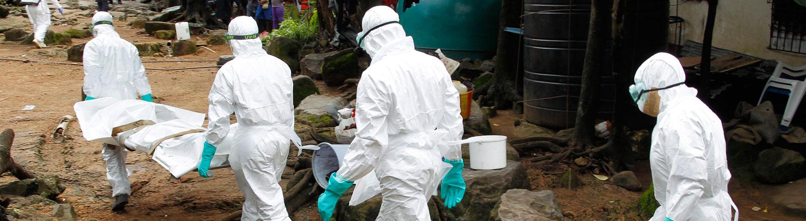 Fachpersonal in Schutzanzügen trägt einen Ebola-Toten auf einer Bahre weg.