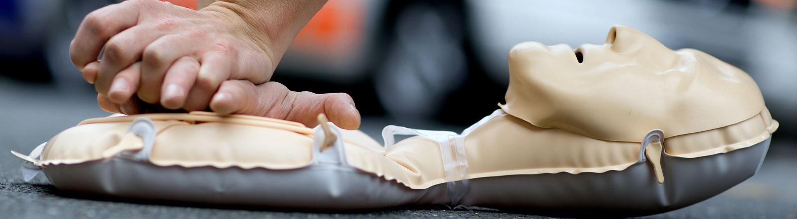 Ein Mann übt Reanimation anhand einer auflblasbaren Puppe.